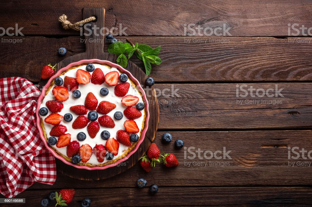 Delicious strawberry pie with fresh blueberry and whipped cream on wooden rustic table, cheesecake, top view stock photo