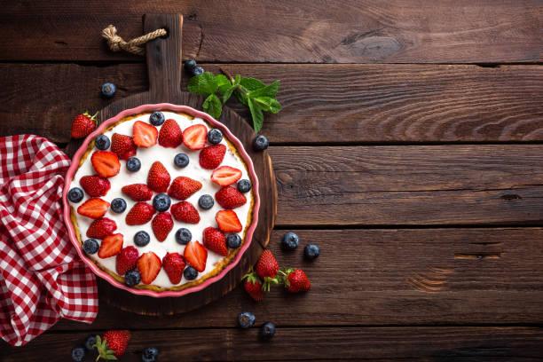 köstliche erdbeer torte mit frischen blaubeeren und schlagsahne auf rustikalen holztisch, käsekuchen, ansicht von oben - obst käsekuchen stock-fotos und bilder
