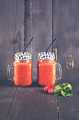 Healthy strawberry smoothie in a mason a jar glass with scattered berries over a rustic wood background. healthy food for breakfast and snack
