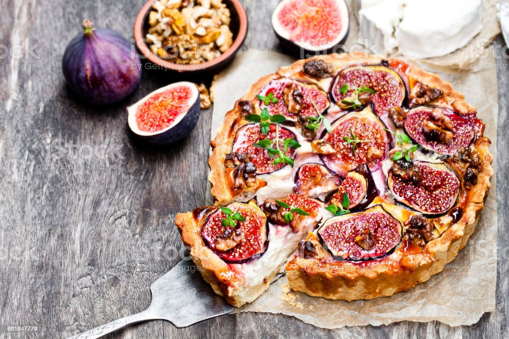 Delicious  tart with fresh figs and goat cheese on rustic wooden table stock photo