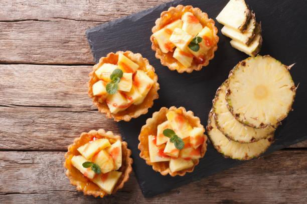 leckere törtchen mit frischer ananas und marmelade closeup auf dem tisch. horizontale ansicht von oben - ananaskuchen stock-fotos und bilder