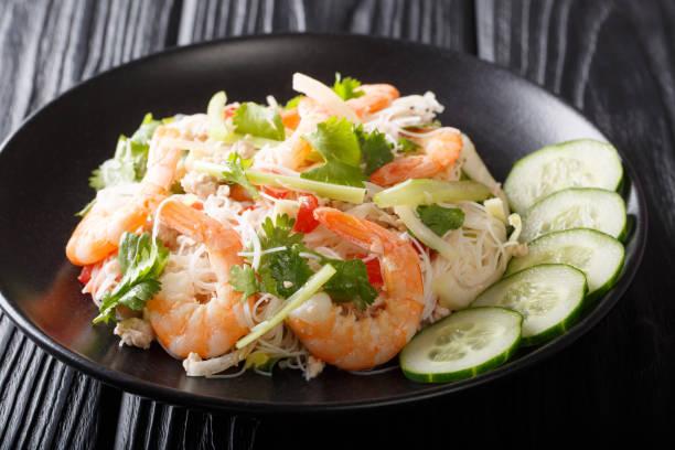 köstlicher thailändischer salat yum woon sen mit meeresfrüchten und gemüse aus nächster nähe auf einem teller. horizontal - erdnusssalatdressings stock-fotos und bilder