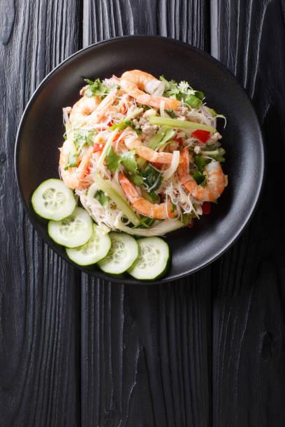 köstlicher thailändischer salat yum woon sen mit meeresfrüchten und gemüse aus nächster nähe auf einem teller. vertikale obere ansicht - erdnusssalatdressings stock-fotos und bilder