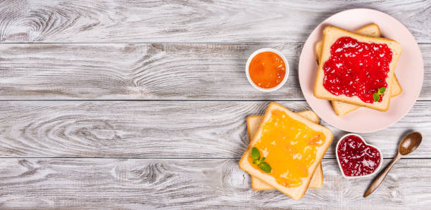 Delicious toasts with various sweet jams on grey background. Copyspace for your text, banner. stock photo