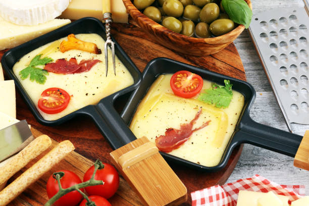 délicieux fromage de raclette suisse fondu traditionnel sur pommes de terre bouillies ou cuites en dés et baguette servie dans des poêles individuelles avec du salami. - raclette photos et images de collection
