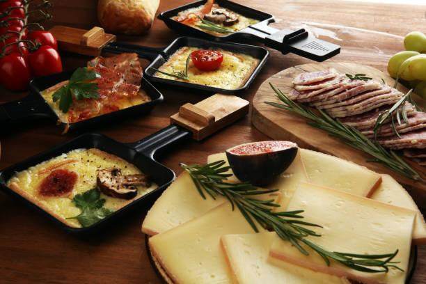 délicieux fromage de raclette fondu suisse traditionnel sur des pommes de terre bouillies ou cuites au four en dés. - raclette photos et images de collection
