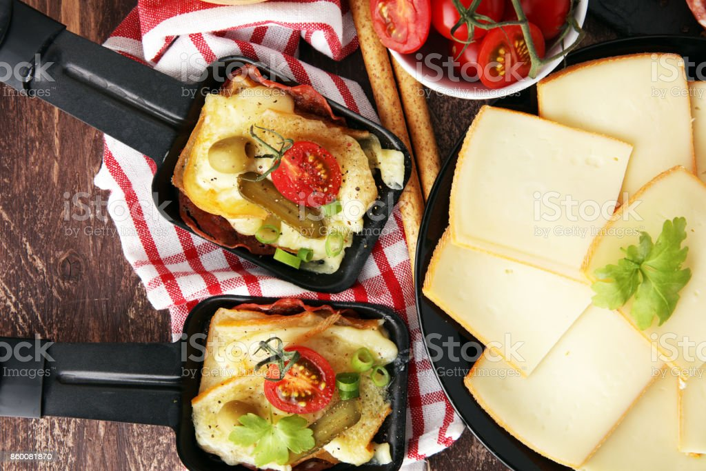 Delicious traditional Swiss melted raclette cheese on diced boiled or baked potato served in individual skillets with salami stock photo