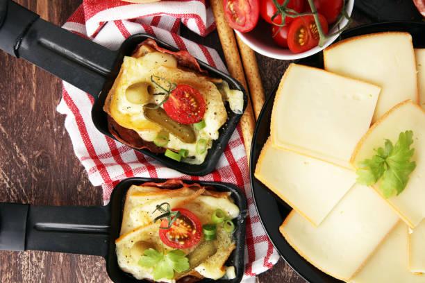 suisse traditionnelle délicieuse fondue fromage à raclette sur dés pommes de terre bouillies ou cuites au four servi dans des poêlons individuels avec sarah - raclette photos et images de collection