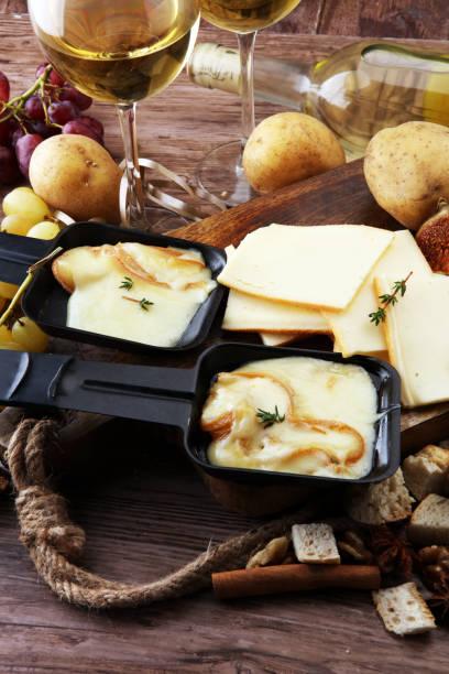 suisse traditionnelle délicieuse fondue fromage à raclette sur dés pommes de terre bouillies ou cuites au four servi dans des poêlons individuels. - raclette photos et images de collection