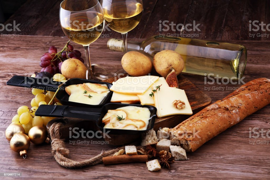 Delicious traditional Swiss melted raclette cheese on diced boiled or baked potato served in individual skillets. stock photo