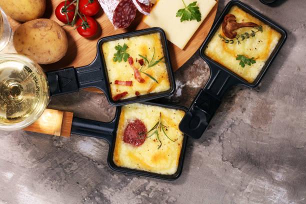 suisse traditionnelle délicieuse fondue fromage à raclette sur pomme de terre bouillie ou cuite en dés. - raclette photos et images de collection