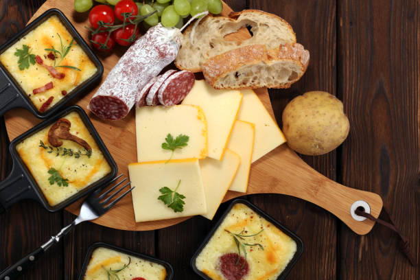 Delicious traditional Swiss melted raclette cheese on diced boiled or baked potato. stock photo
