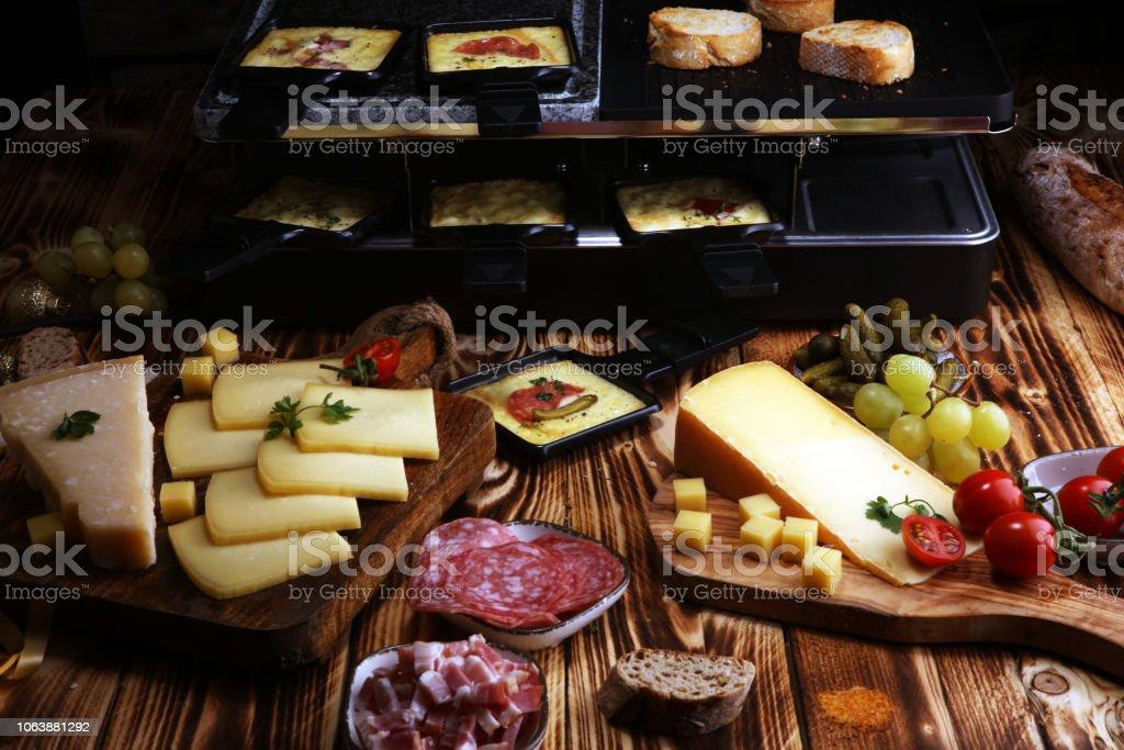 Köstliche traditionelle Schweizer geschmolzen Raclette-Käse in einzelnen Bratpfannen mit Salami serviert. - Lizenzfrei Deutschland Stock-Foto