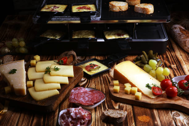 suisse traditionnelle délicieuse fondue fromage à raclette servie dans des poêlons individuels avec sarah. - raclette photos et images de collection