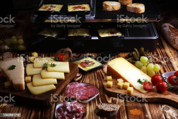 Köstliche Traditionelle Schweizer Geschmolzen Raclettekäse In Einzelnen Bratpfannen Mit Salami Serviert Stockfoto und mehr Bilder von Deutschland