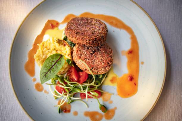 deliciosas hamburguesas veganas hechas de vigas de soja con arroz amarillo y ensalada. - vegana fotografías e imágenes de stock
