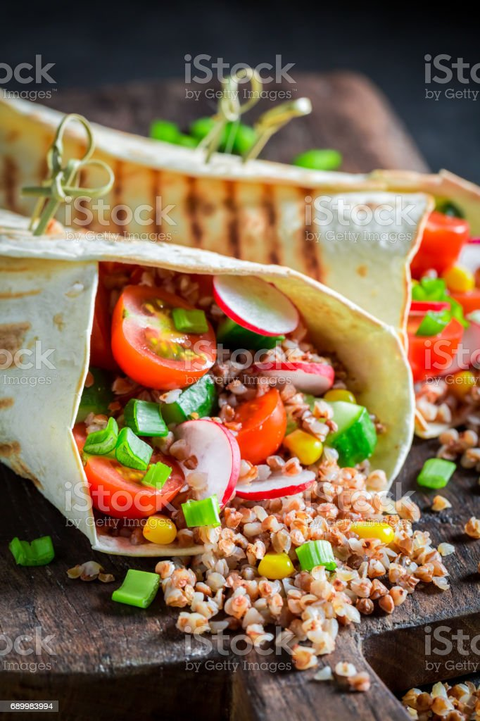 Delicious vegetarian tortilla with groats, cherry tomatoes and radish stock photo