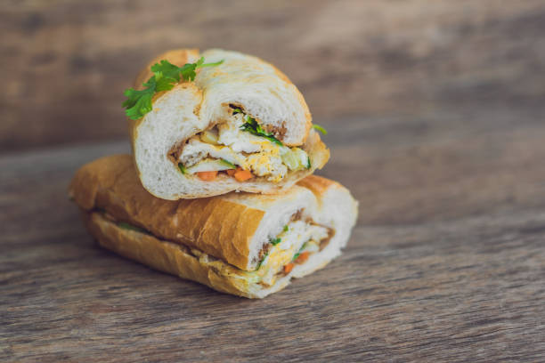 A delicious Vietnamese Bahn Mi sandwich on a wooden background A delicious Vietnamese Bahn Mi sandwich on a wooden background. bánh mì sandwich stock pictures, royalty-free photos & images