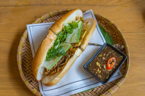 Delicious Vietnamese chicken banh mi served on traditional rattan tray Tasty Vietnamese chicken banh mi served on traditional rattan tray bánh mì sandwich stock pictures, royalty-free photos & images