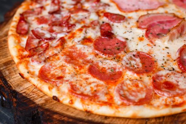 Delicious yummy fresh pizza with bacon, salami, ham and pepperon Delicious yummy fresh pizza with bacon, salami, ham and pepperoni and appetizing crust, close up. Italian food, pizzeria concept pastry dough stock pictures, royalty-free photos & images