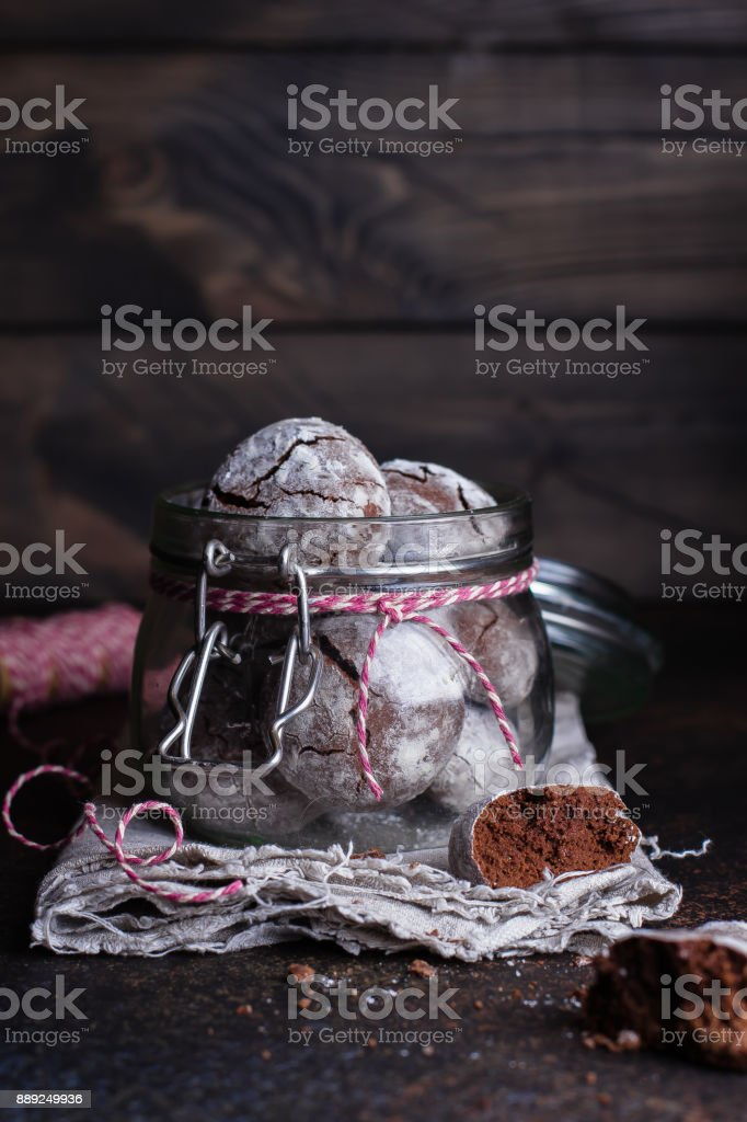 Deliciouse Homemade Chocolate crinkle cookies with powdered sugar icing in glass jar on dark stone table background. stock photo