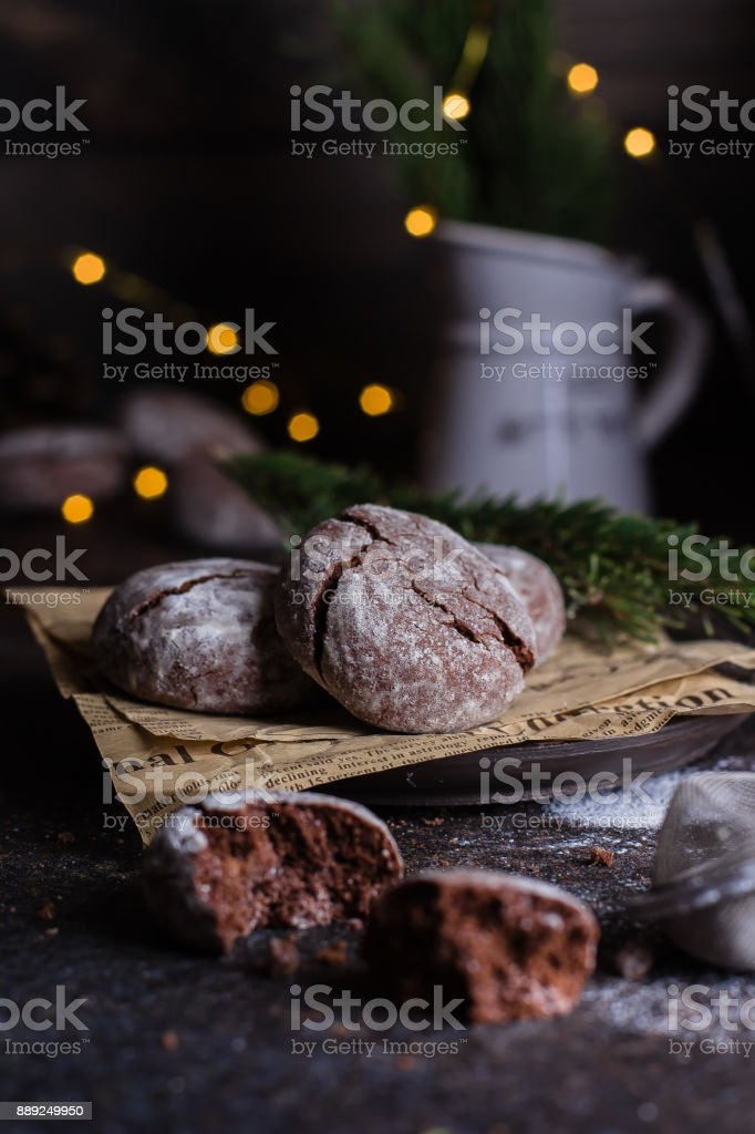 Deliciouse Homemade Chocolate crinkle cookies with powdered sugar icing on dark stone table background. Holiday Decoration, lights, garland stock photo