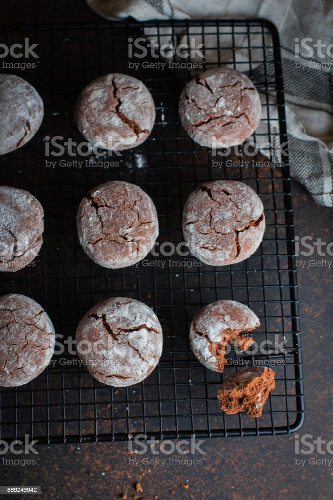 Deliciouse Homemade Chocolate crinkle cookies with powdered sugar icing grate for cooling on dark stone table background. Top view stock photo