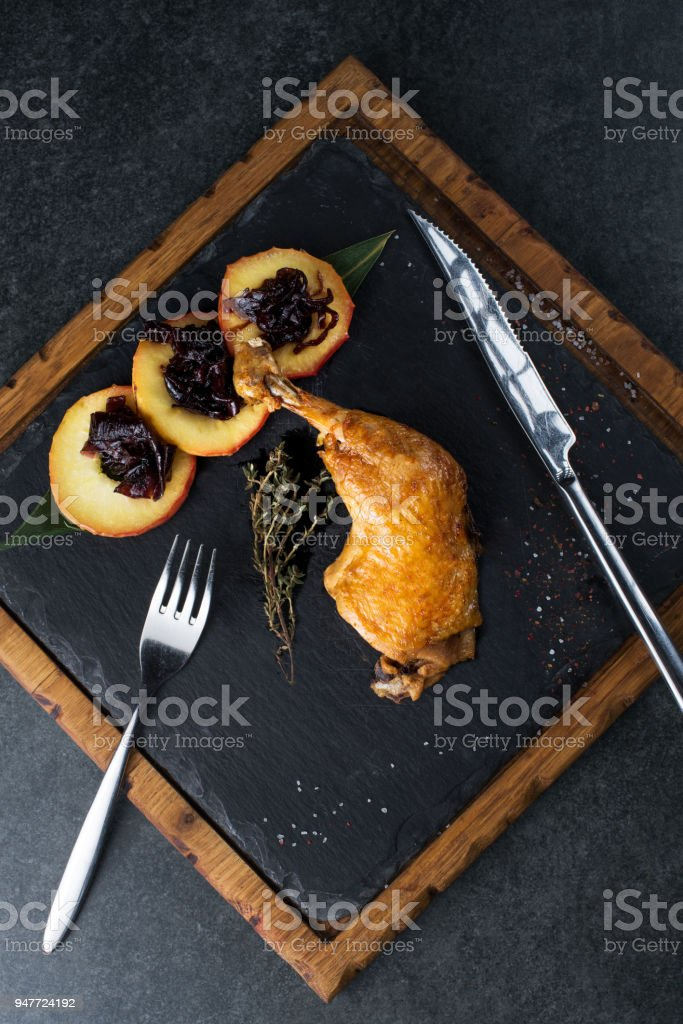Deliciously cooked duck leg on a black plate stock photo