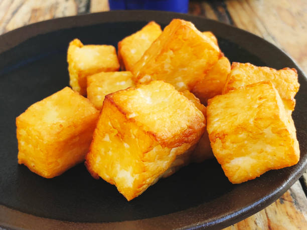 Deliciously fried cheese cubes on a dark plate. stock photo