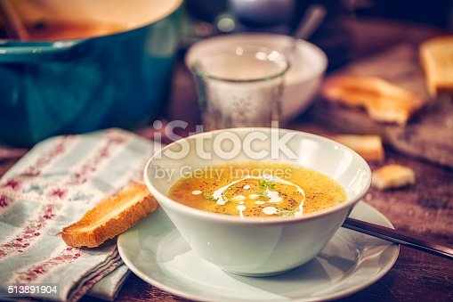 Delicous chicken soup with carrots, onions and parsnips. The soup is served in a bowl with creme fresh and grilled toast.
