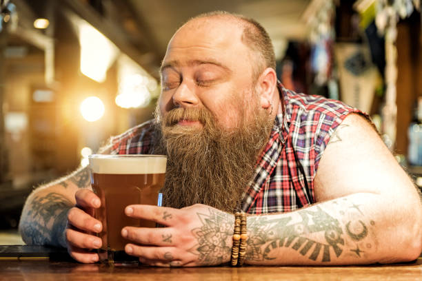 Delight bearded male drinking beverage in pub stock photo