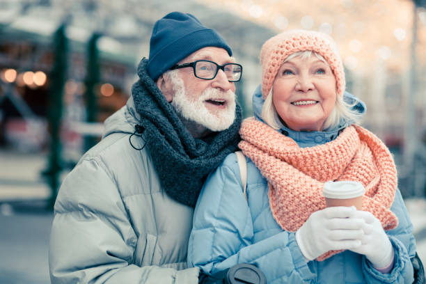 Delighted aged couple in the street smiling and looking away stock photo