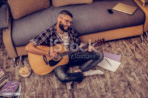 istock Delighted artistic bearded man playing the guitar 1098011966