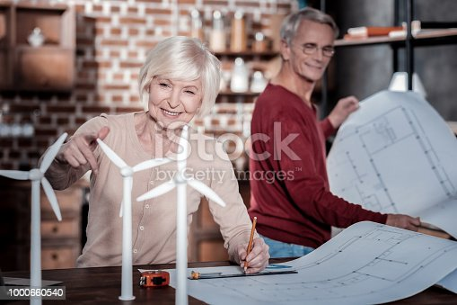 istock Delighted blonde playing with wind turbines 1000660540