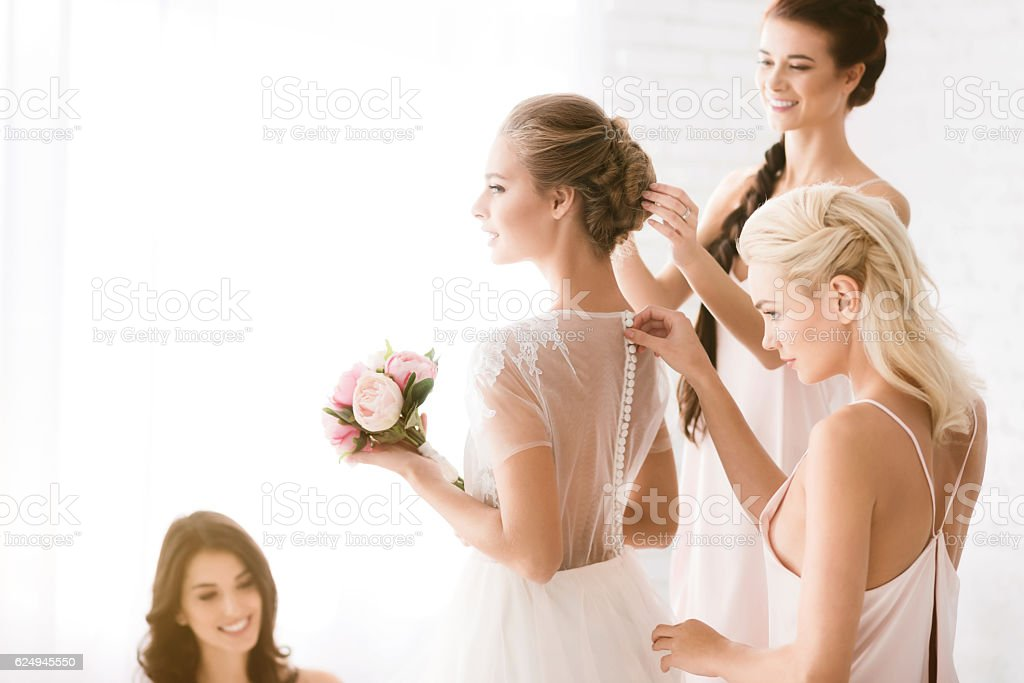 Delighted bridesmaids helping the bride to get ready – Foto
