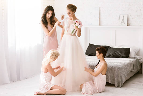Delighted bridesmaids helping the bride to get ready stock photo