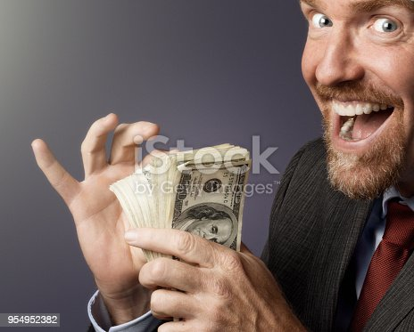 Businessman gloats over his pile of cash.