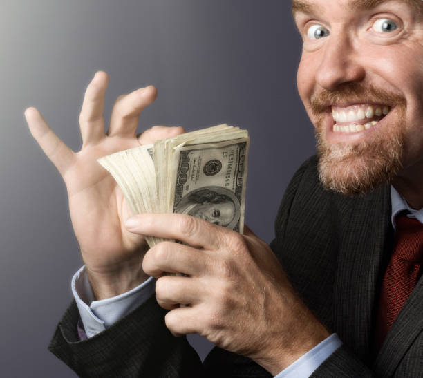 Delighted businessman counts his stack of money Businessman gloats over his pile of cash. greed stock pictures, royalty-free photos & images