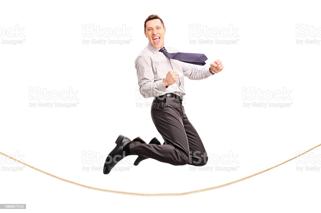 Delighted businessman jumping over a rope stock photo