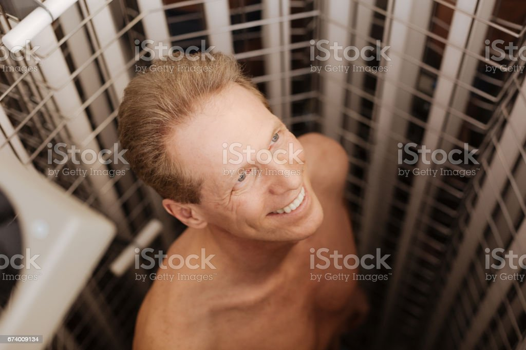 Delighted charismatic man getting tanned in the tanning both royalty-free stock photo
