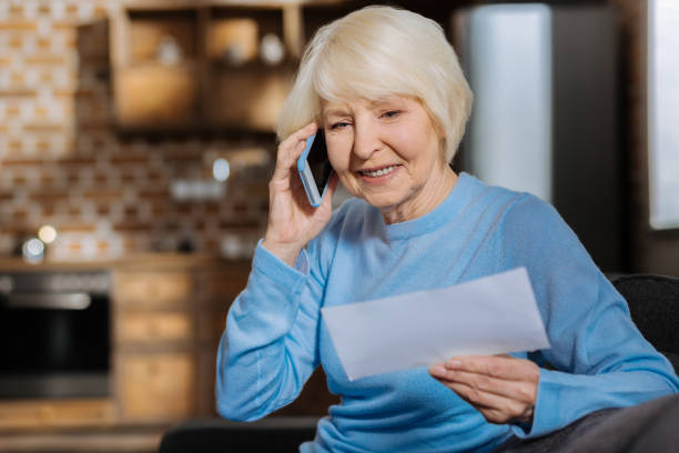 delighted elderly woman making a phone call - social security check stock photos and pictures