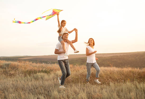 Delighted family playing with kite stock photo