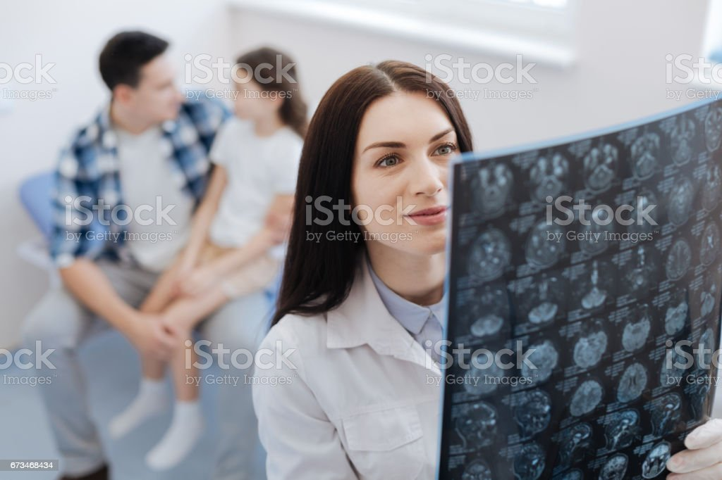 Delighted female doctor looking at the X ray scan image stock photo