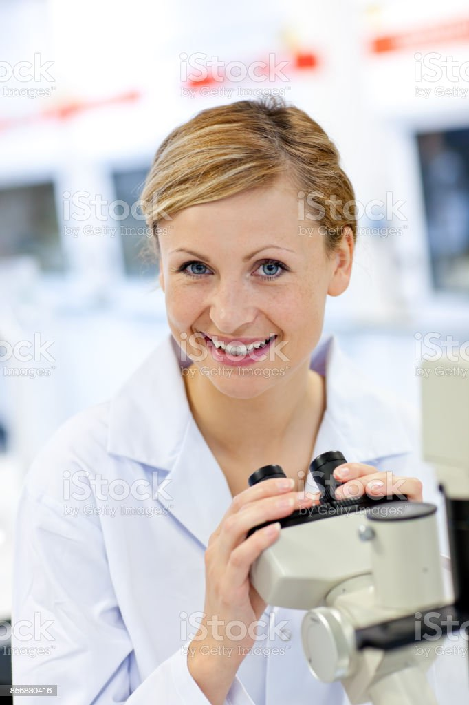 Delighted female scientist using a microscope stock photo