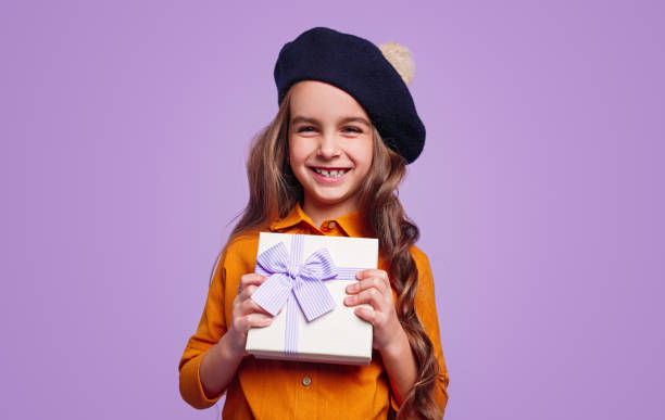 Delighted girl in hat showing gift box stock photo