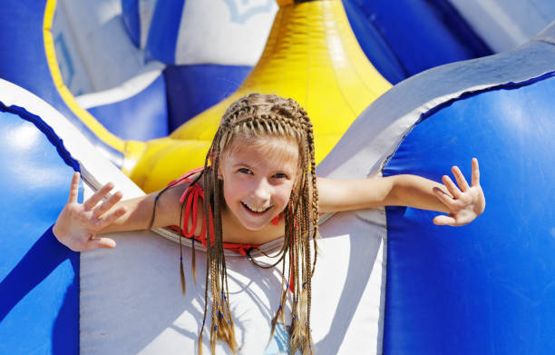 delighted girl on inflatable attraction - school fete stock photos and pictures