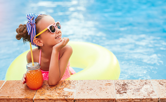 Positive child with jar of fresh fruit drink smiling and looking away while resting in pool near border on summer day on resort
