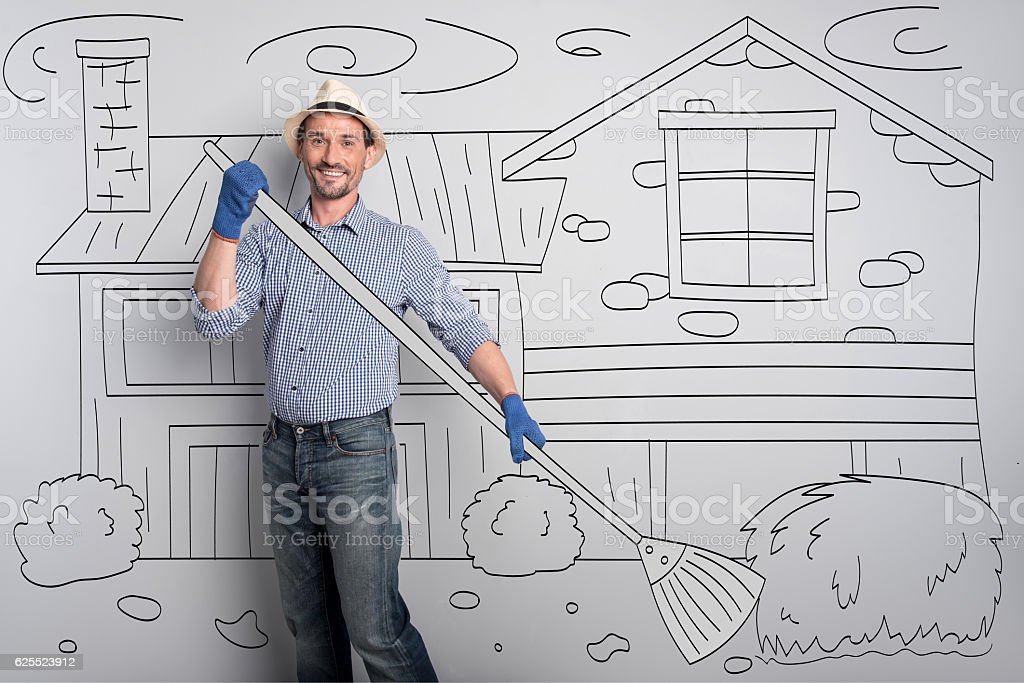 Delighted happy farmer cleaning the yard. stock photo