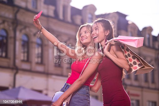 Our photo. Delighted joyful women looking in the smartphone camera while taking a selfie together