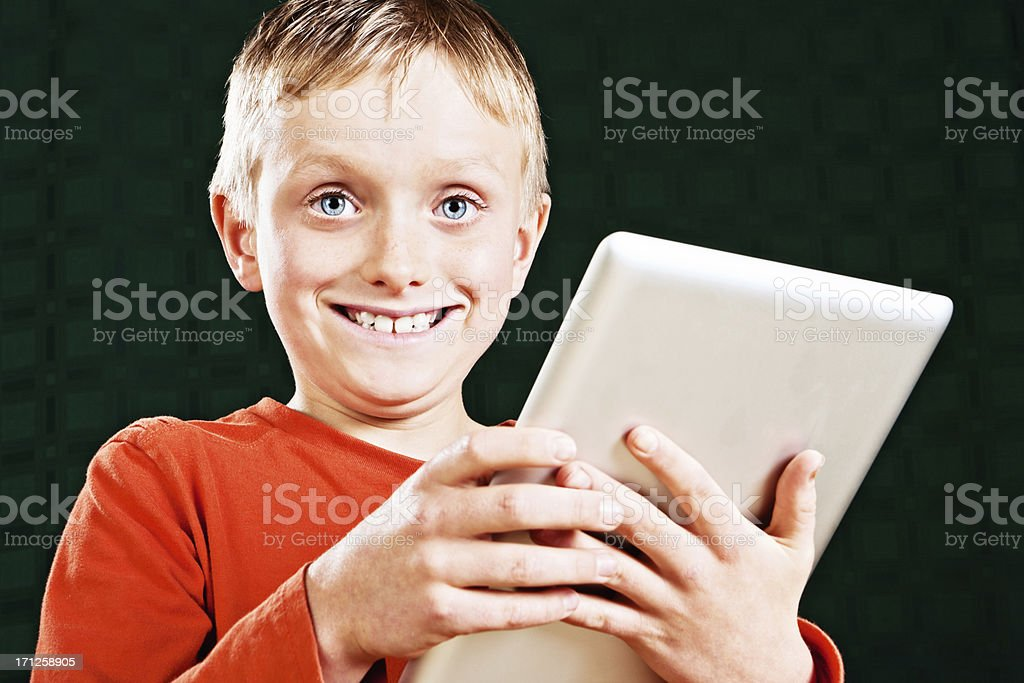 Delighted little blond boy smiling with new tablet pc royalty-free stock photo